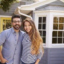 Excited-couple-standing-outside-new-home-best-mortgage-brokers